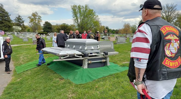Man at attention for Veteran's coffin in cemetery
