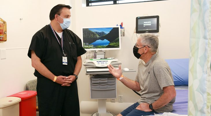 Doctor talks with male patient in exam room