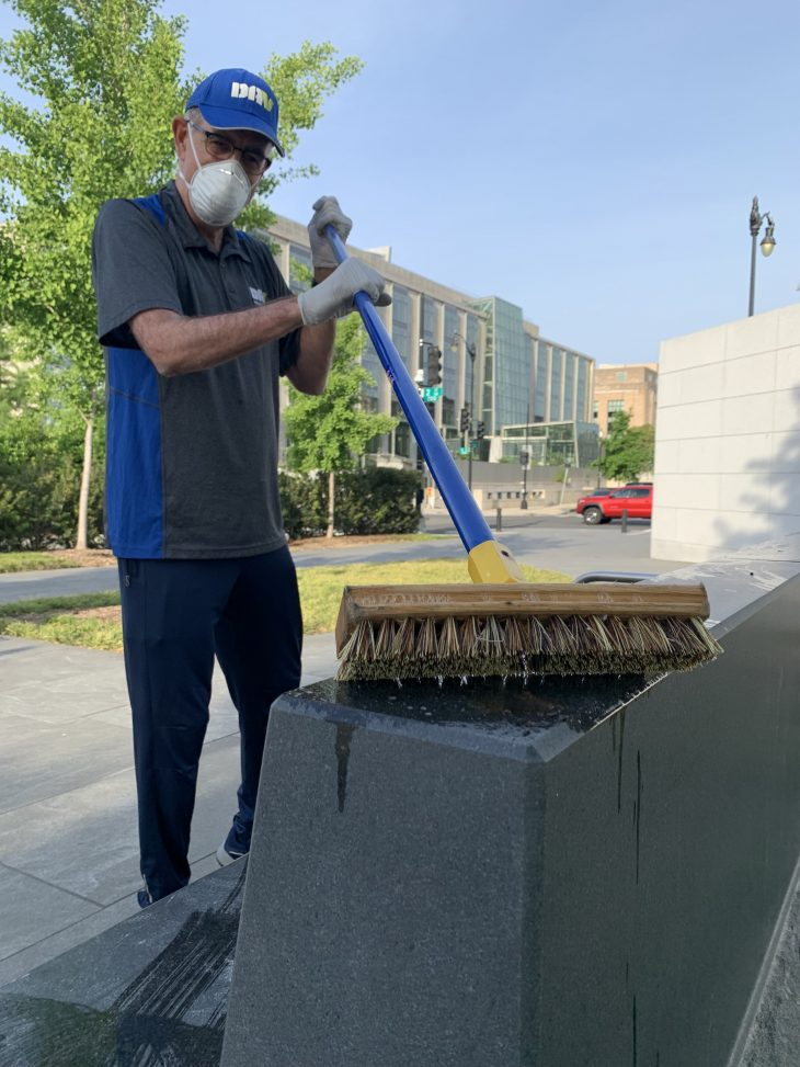 Army Vietnam Veteran Gary Salpini cleans a bench at the American Veterans Disabled for Life Memorial in Washington, D.C.