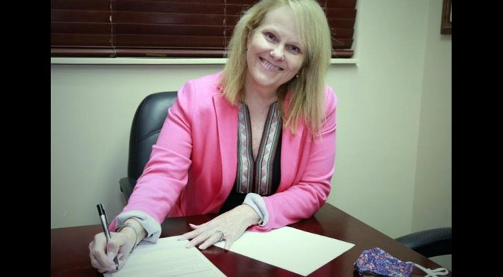 Smiling woman in pink jacket signing papers