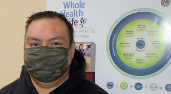 Man in mask in front of Whole Health poster