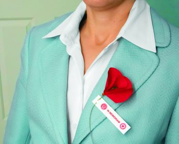 womans lapel with red poppy pinned to it