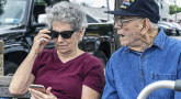 An elderly Veteran sits with his caregiver daughter as they review her phone