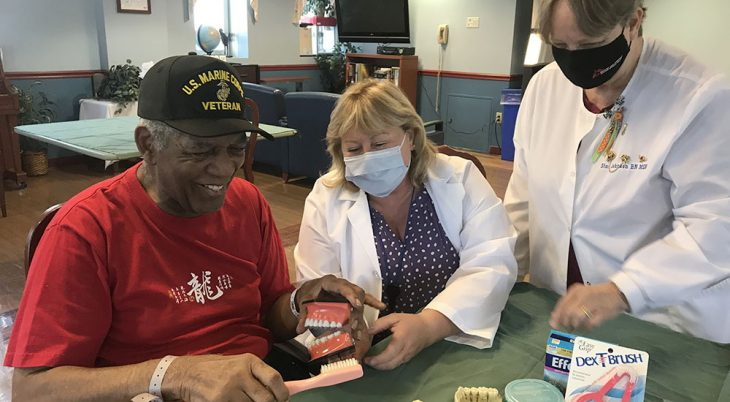A dentist and a nurse demonstrate proper brushing to a Veteran
