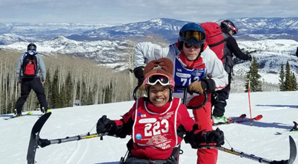 Female Veteran and her adaptive ski instructor prepare for a day on the slopes