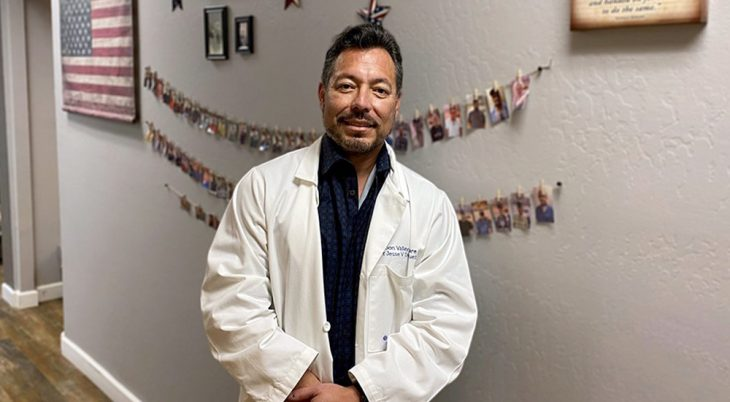 Doctor standing in front of wires holding numerous photos