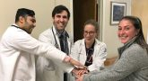 Four young doctors stacking hands