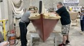 Two men working on the interior of a sailboat