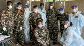 Ten people in fatigues and masks ready to vaccinate