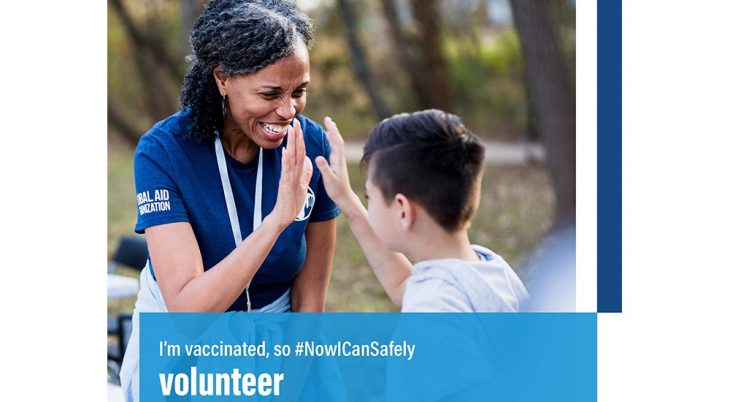 """A smiling young woman and a young boy, outdoors, exchanging a high-five, with the caption, """"I'm vaccinated, so now I can safely volunteer"""""""