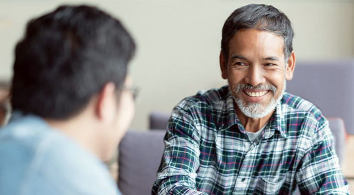 Smiling man talking with another man