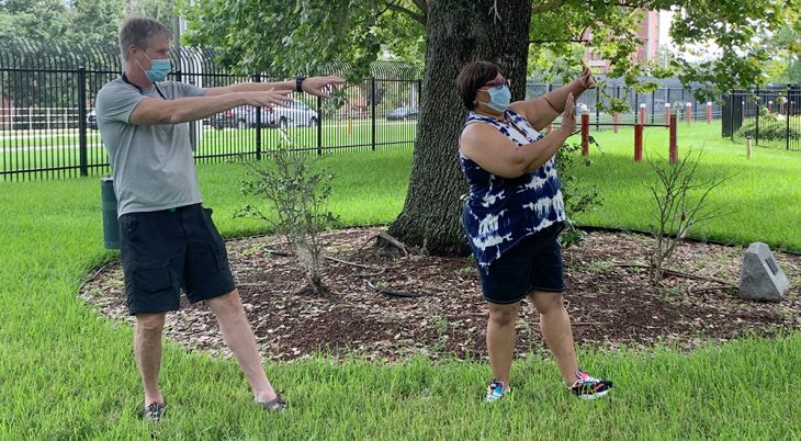 Man and woman doing tai chi in a park