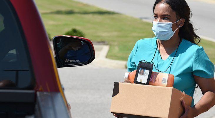 Woman wearing mask prepares to hand box of food to person in vehicle