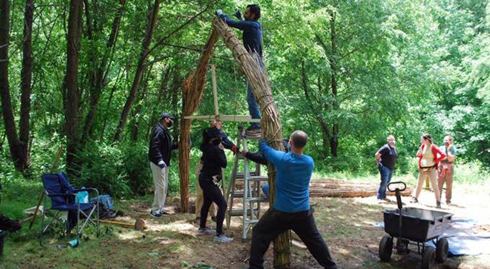 Several people work together to tie reeds for a structure that will be a place of healing