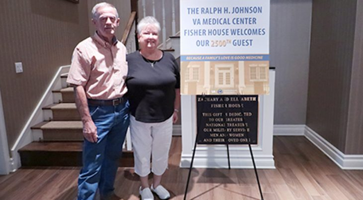 Veteran and wife next to poster welcoming 2500th Veteran
