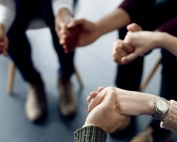 Members of a counseling circle hands as they discuss military sexual trauma