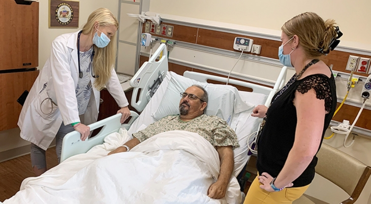 Doctor and spouse talk with man in hospital bed about immunotherapy