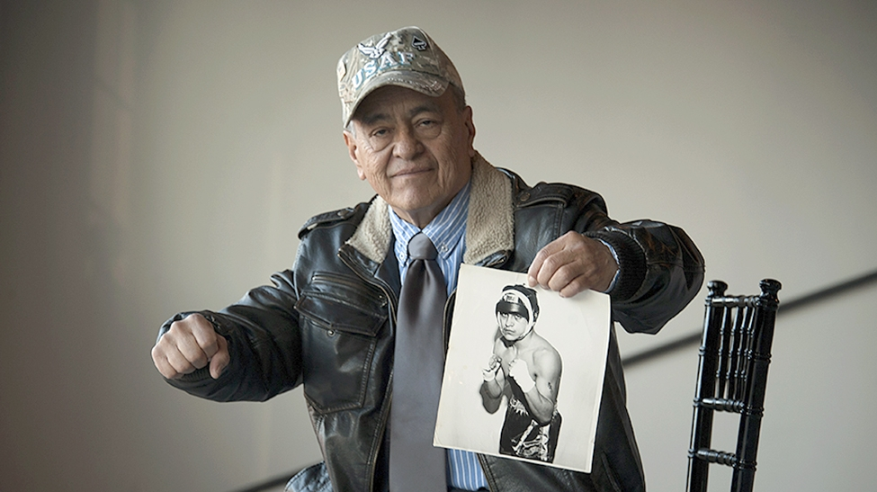 Man holding a photo of himself younger and in boxing gear