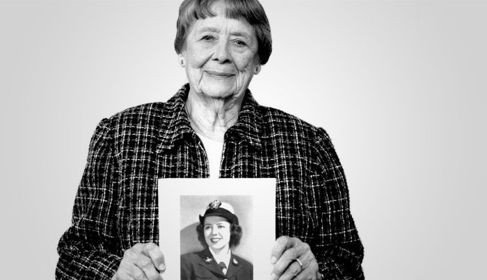 Julia Parson holding a photo of her in uniform.