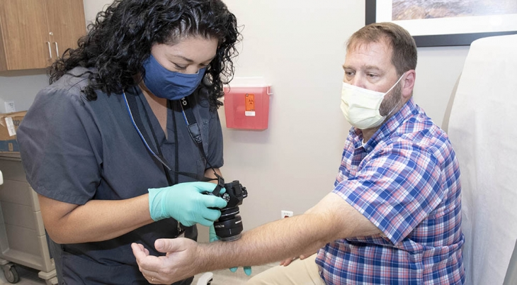 Outpatient clinic technician takes dermatology images of Veteran's arm