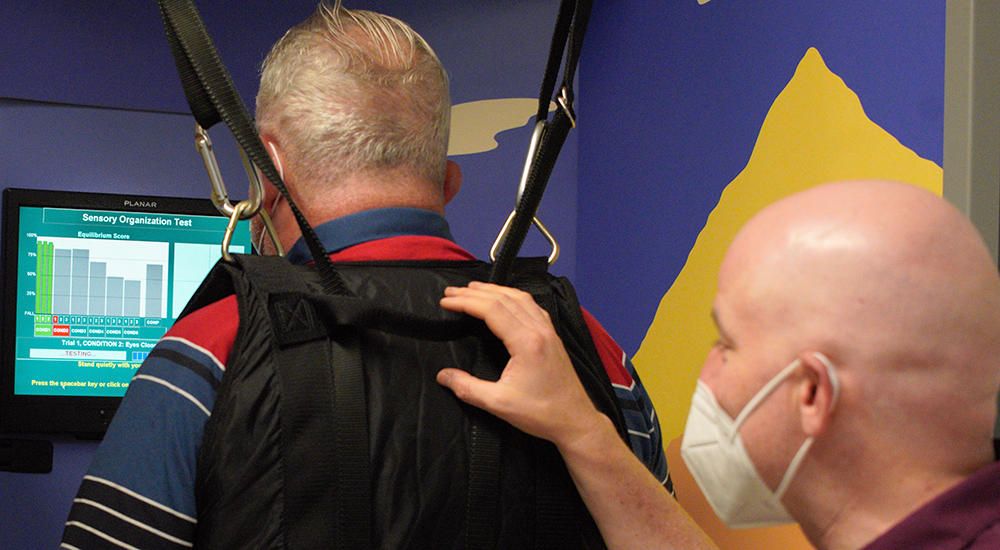 A technician helps a man find his balance while wearing a halter