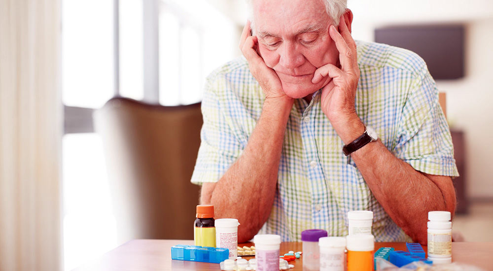 Senior man sitting and looking at his prescriptions medication from a community providers