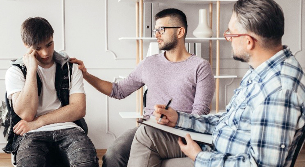 Man comforts man in PTSD group counseling session