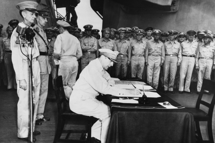 Army Gen. Douglas MacArthur signs the Instrument of Peace as the supreme allied commander during formal Japanese surrender ceremonies on the USS Missouri in Tokyo Bay, Sept. 2, 1945. Standing behind MacArthur are Army Lt. Gen. Jonathan Wainwright, left; and British Lt. Gen. A. E. Percival, commander of Singapore.