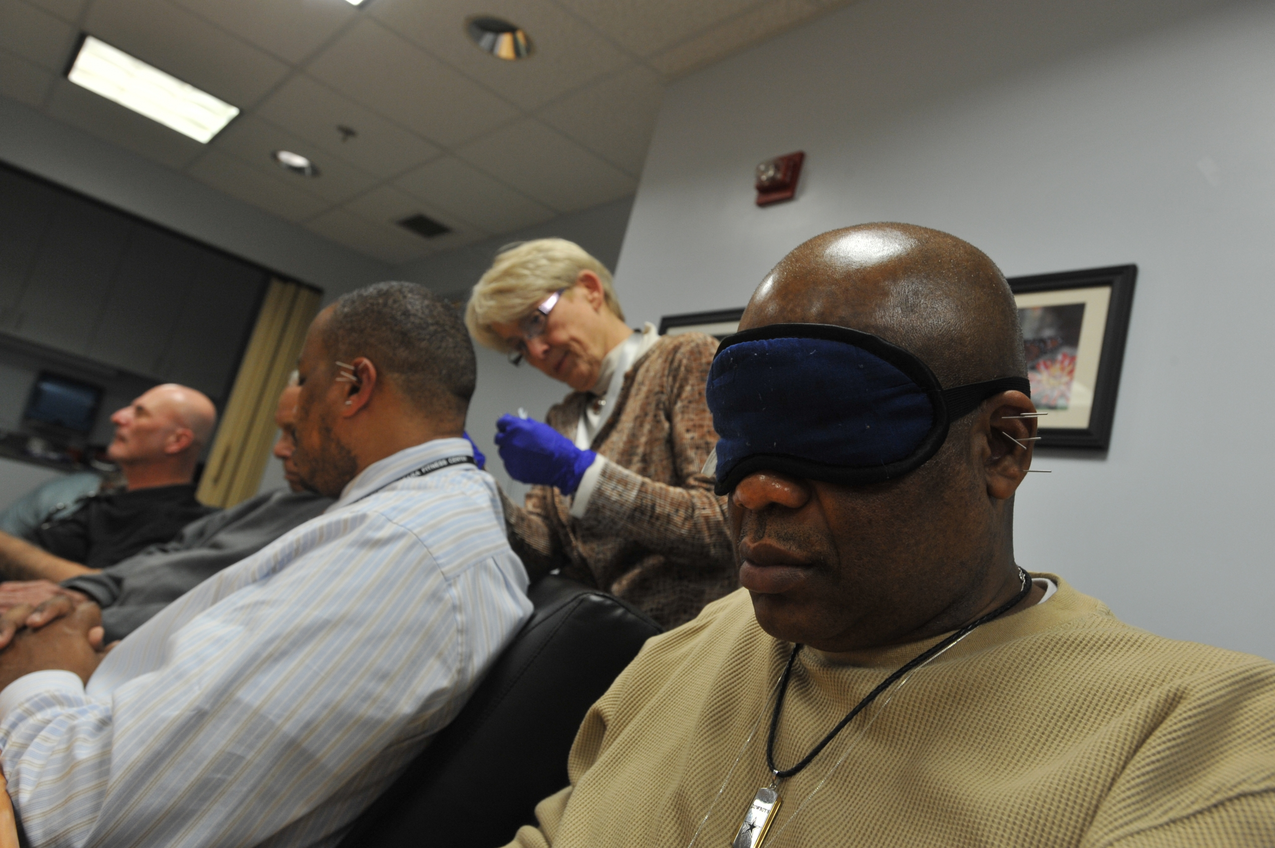 Veterans receive battlefield acupuncture treatment at the Washington DC VA Medical Center. An eye mask and soothing music in the background help create a relaxing environment.