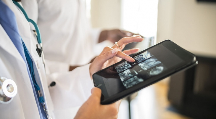 A Telestroke health care provider looks at clinical images on a tablet