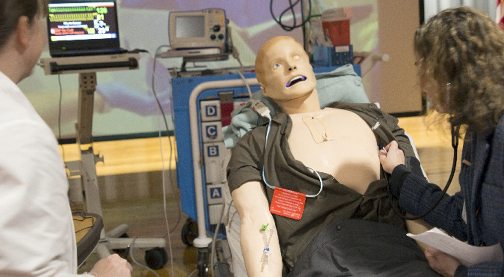 Two nurses practice procedures on manikin patient at the simulation center