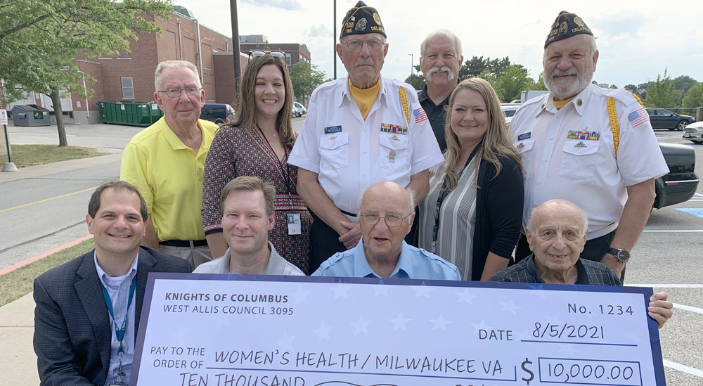 Ten people holding giant check for $10,000 to go to moms