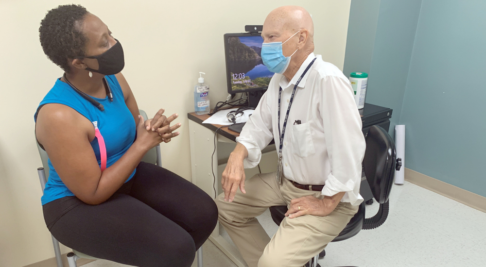 Woman participant in the Breast Cancer Survivorship program talks with her male doctor