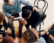 A group of people console a young man in alcohol and drug therapy