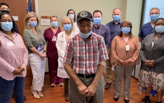 Senior Veteran surrounded by VA staff at Little Rock ceremony
