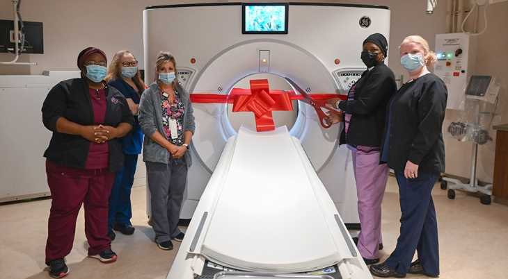 Five nurses and technician at CT scanning machine ribbon cutting