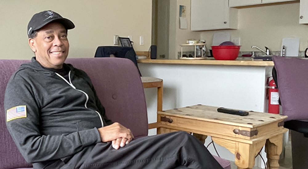Smiling Veteran sitting in home thanks to housing support