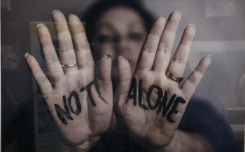 woman holding up hands with words not alone written on her palms