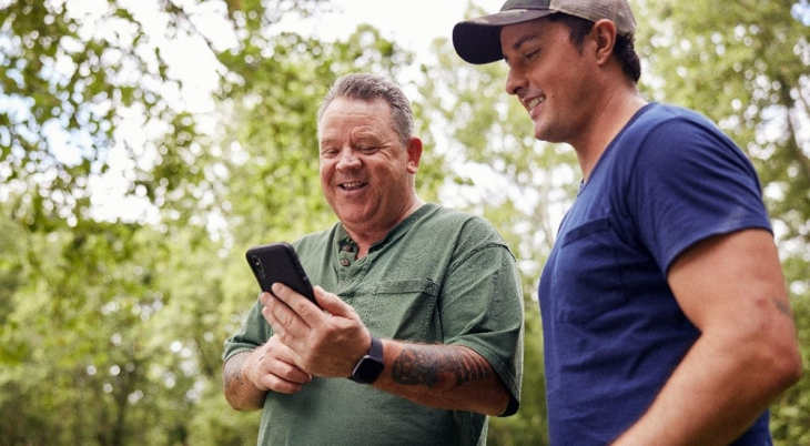 Two male Veterans, one looking at Annie App on his cell phone