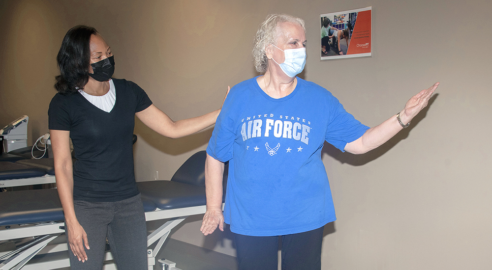 Physical therapist assisting older Veteran in therapy session
