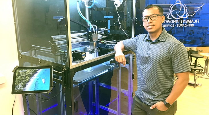 Man standing next to large 3D printer used to create prosthetics