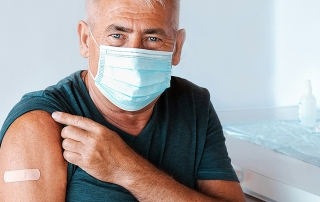 Man wearing mask shows COVID vaccination bandage, lottery