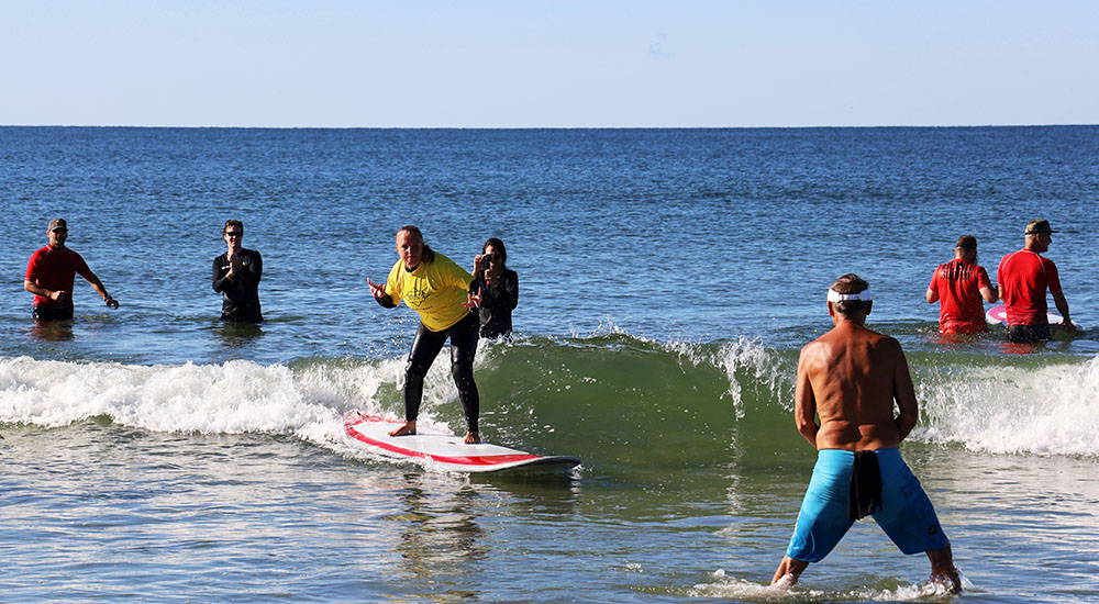 A Veteran riding surfboard in low surf